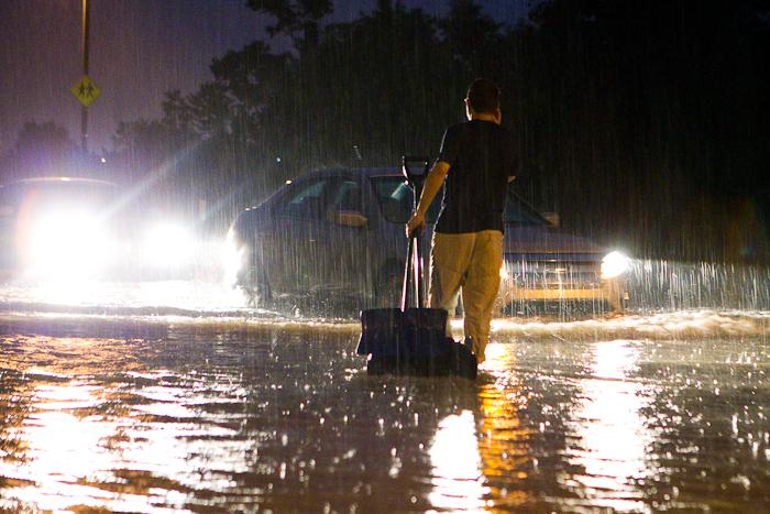 Un résident du quartier tente d'empêcher les véhicules de continuer leur chemin sur une rue entièrement inondée. Gatineau - Secteur Hull (Le Plateau), 24 juin 2011. (© Sébastien Lavallée, 2011)